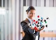 Businesswoman holding molecule model in office