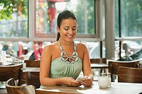 Germany, Munich, Young woman using mobile in cafe, smiling