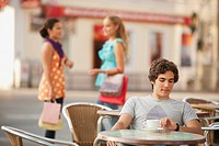 Germany, Munich, Young man waiting at cafe with friends in background