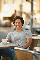Germany, Munich, Young man in cafe, smiling, portrait