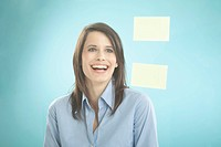 Businesswoman looking at adhesive notes, smiling (thumbnail)