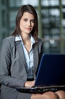 Germany, Bavaria, Business woman using laptop, portrait (thumbnail)