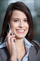 Germany, Bavaria, Business woman on the phone, smiling, portrait