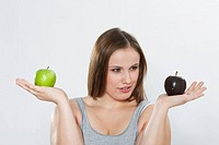 Young woman confused between green apple and chocolate coated apple