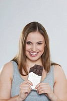 Young chubby woman with chocolate bar, smiling, portrait