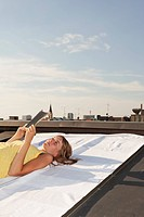 Germany, Bavaria, Munich, Young woman eading a book on a rooftop