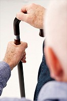 Senior man  detail  seen from behind waiting with his hand on a crutch in a clinic waiting room or medical center