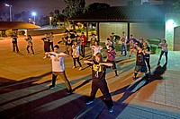 An Asian American college student conducts an informal night hip hop dancing class outdoors on the campus of Saddleback College in Southern California