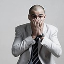 Portrait of a businessman covering his mouth with his hands