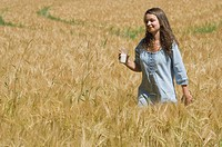 Germany, Munich, Teenage girl with glass of milk in cornfield