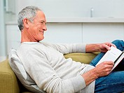 Senior man sitting on sofa reading book