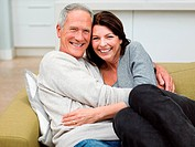 Mature couple embracing on sofa
