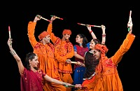 Men and women performing dandiya