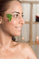 Woman with a leaf on her face smiling in health spa
