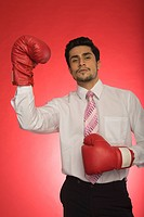 Portrait of a businessman wearing boxing gloves (thumbnail)