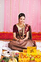 Bride sitting near a havan kund at the wedding mandap