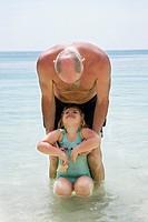 Senior man with girl child in beach