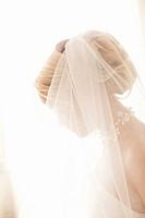 Backlit profile of bride wearing vial