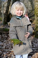 Five year old girl showing a piece of moss she has found on a nature walk