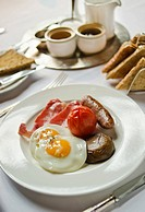 Plate with English breakfast on table