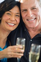 Happy mature couple with flutes