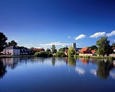 England, Norfolk, Great Massingham. View across one of several large ponds towards the picturesque village of Great Massingham.