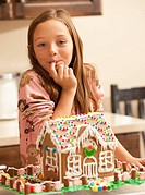 Portrait of girl 6_7 licking finger by gingerbread house