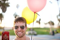 Caucasian man holding two balloons