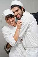 Bakers hugging in bakery kitchen