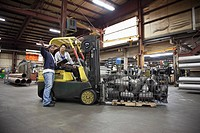 Workers with forklift in factory
