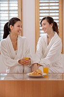 Women in bathrobes chatting while enjoying their drinks