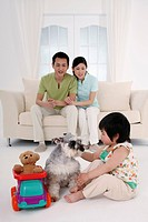 Girl playing with dog, parents watching