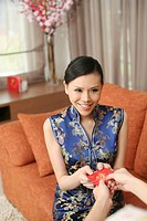 Woman in cheongsam receiving red packet