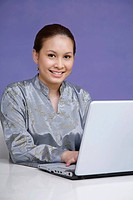 Woman in baju kurung smiling at the camera while using laptop