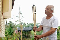 Senior man holding bamboo torch