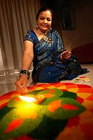 Woman drawing kolam on the floor