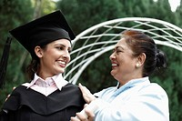 Senior woman and woman in graduation gown smiling at each other