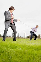 Two businessmen playing tug of war in a field