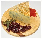 Bleu de Gex or Bleu du Haut-Jura or Bleu de Septmoncel French blue cheese with black grape on wooden board