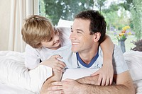 Man smiling with his son on the bed