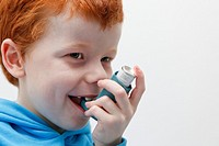 Little boy using his asthma inhaler to alleviate symptoms