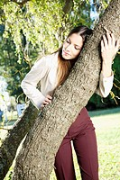 Teenage girl hugging a tree