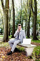 Businessman talking on a mobile phone while working on a laptop