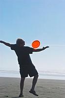 Man playing freestyle frisbee on California beach