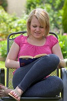 Teenage girl sitting in a garden reading a book, England