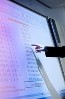 A man presenting a spreadsheet of figures on a digital whiteboard