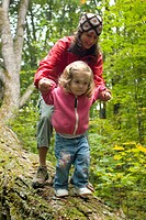 Young woman and child exploring in forest in rural Lake Ossipee, New Hampshire.