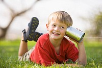 A smiling young boy plays the telephone game by listening into into a tin can with a string attached to it on a sunny summer day.