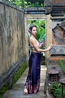 A young woman standing in the grounds of a resort in Bali, Indonesia.