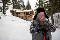 Bearded man with snow shovel in front of house in winter, Whitefish, Montana.